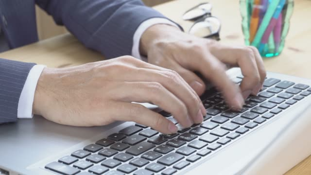 Businessman-in-Suit-Typing-Laptop-in-Home-Office-Close-Up-View