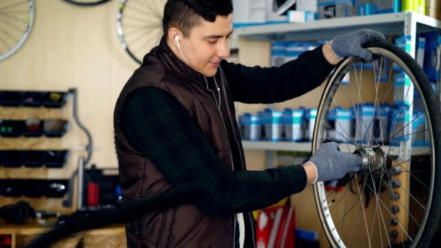 Reparador-de-jóvenes-es-la-limpieza-del-rueda-de-la-bicicleta-dentro-y-fuera-sucio-pedazo-de-paño-y-escuchando-música-con-auriculares-Concepto-de-profesión-y-personas-