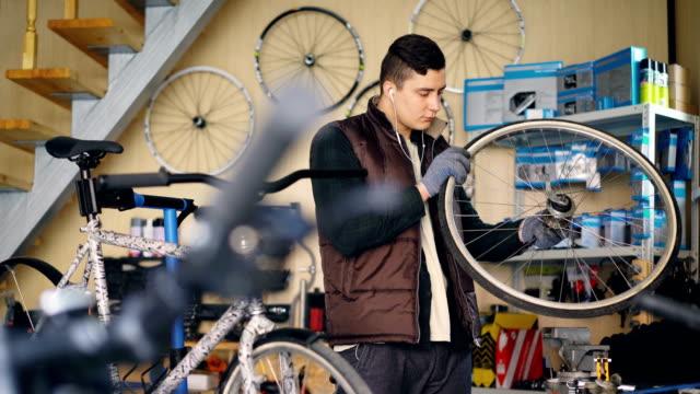 Mecánico-experimentado-está-girando-la-rueda-de-bicicleta-de-comprobación-de-trabajo-del-mecanismo-y-escuchando-música-mientras-trabajaba-en-el-pequeño-taller-Concepto-de-mantenimiento-y-personas-
