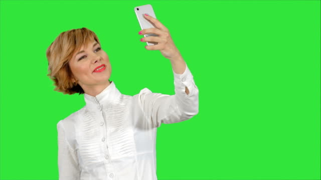 Businesswoman-taking-funny-selfie-with-phone-on-a-Green-Screen-Chroma-Key