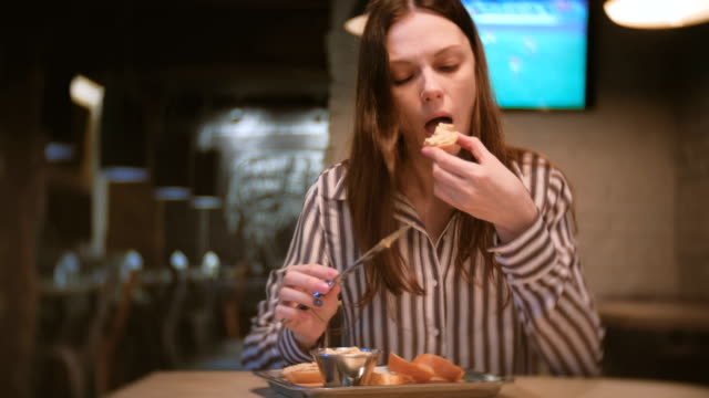 Young-beautiful-woman-brunette-smears-pate-on-a-piece-of-bread-in-cafe-with-knife-And-she-eats-sandwich-