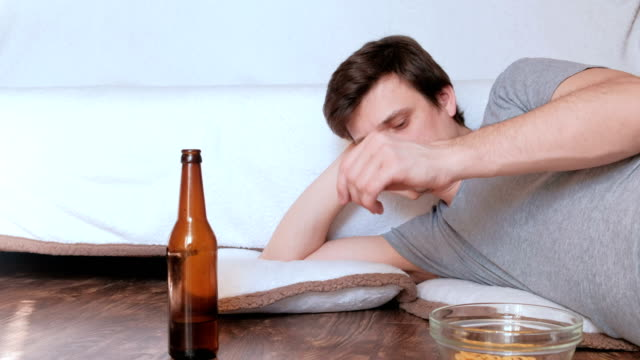 Handsome-young-man-bachelor-throws-the-lid-from-the-beer-bottle-on-the-floor-and-misses-