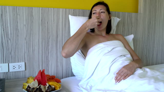 Woman-eating-mango-and-pineapple-lying-in-bed