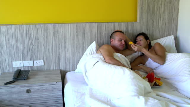 Man-and-woman-are-eating-fruit-lying-in-bed-A-woman-is-feeding-a-mango-man