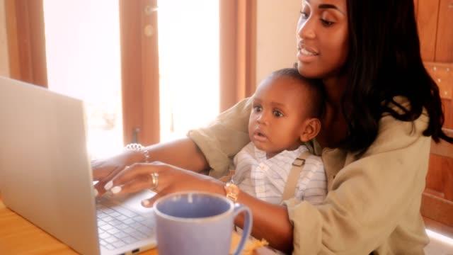 Blogger-Mutter-mit-Baby-auf-Laptop-von-zu-Hause-aus-arbeiten