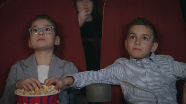 Children-eat-popcorn-in-cinema-Preschool-children-watching-movie-in-cinema