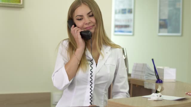 Receptionist-of-clinic-talking-by-phone
