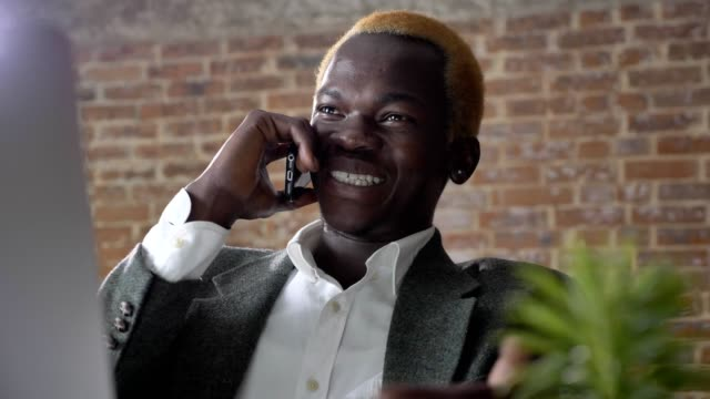 Young-blond-african-american-businessman-talking-on-phone-and-sitting-at-desk-with-laptop-in-modern-office-laughing