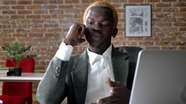 Afrikanischer-Amerikaner-wütend-Jungunternehmer-telefonieren-sitzen-im-modernen-Büro-ernsthafte-und-wütend