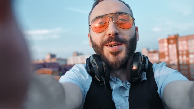 Hombre-feliz-creativo-músico-o-dj-auriculares-de-cuello-tomando-selfie-utilizando-la-cámara-o-smartphone