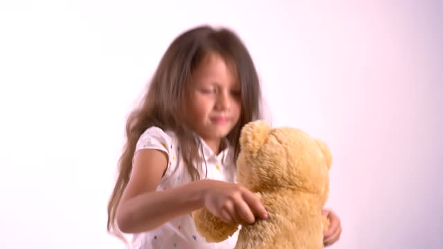 Poco-niño-jugando-con-el-osito-de-felpa-y-baile-celebración-de-juguete-pie-aislado-sobre-fondo-rosa-estudio