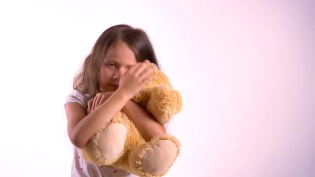Poco-linda-chica-abrazando-a-su-osito-de-felpa-niños-abrazando-juguete-pie-aislaron-sobre-fondo-luminoso-estudio-rosa