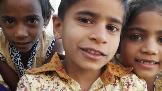 Indian-kids-looking-at-the-camera-smiling-closeup-handheld