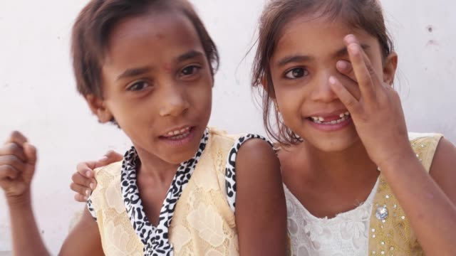 Two-kid-sisters-pointing-their-fingers-at-the-camera-happy-and-smiling