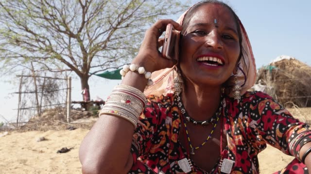 Rural-woman-shy-gregarious-and-laughing-at-using-a-phone-for-the-first-time
