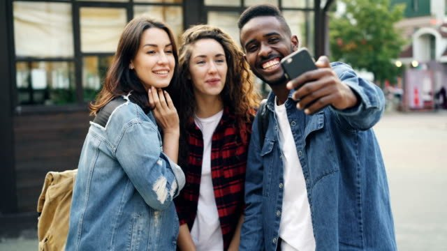 Männliche-und-weibliche-Touristen-multiethnische-Gruppe-nehmen-Selfie-stehen-auf-der-Straße-dann-beobachten-Fotos-und-lachen-Tourismus-Technik-und-Spaß-Konzept-