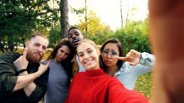 Point-of-view-shot-of-young-woman-holding-device-with-camera-and-taking-selfie-with-friends-multi-ethnic-group-in-park-in-autumn-Photography-and-people-concept-