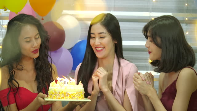 Young-woman-birthday-girl-is-making-wish-blowing-candle-on-cake-and-clapping-hands-while-her-friends-are-congratulating-her-at-the-party-Slow-Motion