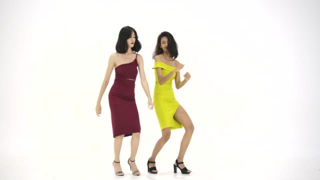 Dos-mujeres-asiáticas-que-se-divierten-bailando-como-locos-en-fondo-blanco-Personas-con-concepto-partido-celebración-disfrute-y-año-nuevo-Cámara-lenta-