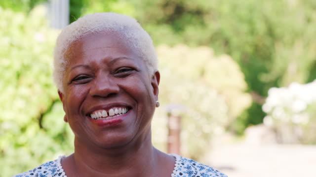 Senior-black-woman-smiling-to-camera-outdoors-close-up