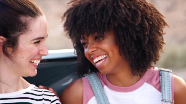 Friends-on-a-trip-sitting-in-car-trunk-at-roadside-close-up