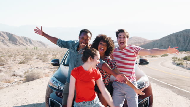 Young-adult-friends-on-road-trip-have-fun-posing-by-the-car