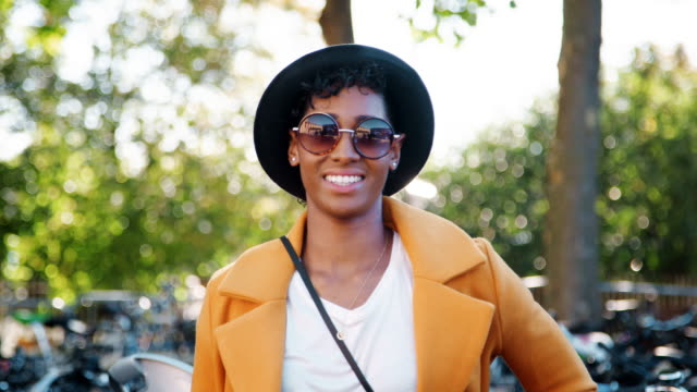 Fashionable-young-black-woman-standing-outdoors-wearing-sunglasses-a-yellow-coat-and-a-black-hat-looking-to-camera-and-laughing-close-up-focus-on-foreground