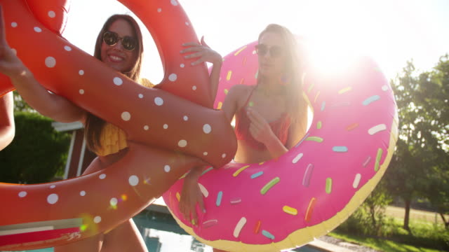 Girls-joking-around-with-novelty-pool-inflatables-with-sunflare
