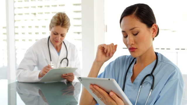 Medical-workers-sitting-at-desk-using-tablet