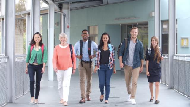 Eine-Gruppe-von-lächelnd-Lehrer-zu-Fuß-in-Richtung-Kamera-in-einem-Korridor