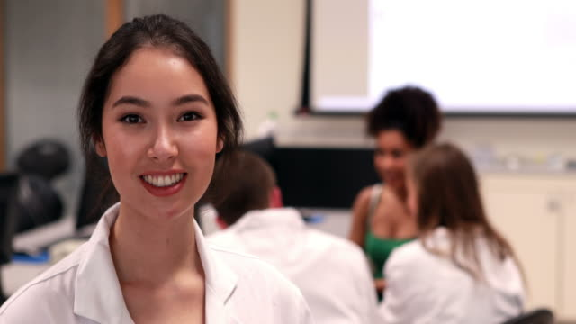 Pretty-medical-student-smiling-at-camera-in-class