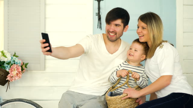 Father-of-happy-family-make-selfie-with-his-wife-and-little-son-in-front-their-home-door