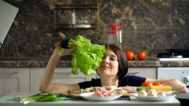 beautiful-smiling-woman-cook-play-with-vegetables-on-table-in-kitchen-at-home