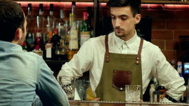 Joven-camarero-hablando-y-sonriendo-a-un-visitante-masculino
