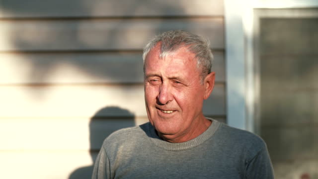 Close-up-portrait-of-smiling-old-man-looking-at-the-camera-laughing-retired-male-standing-in-front-of-sun-4K