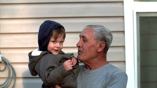 Grandfather-and-grandson-talking-smiling-having-fun-looking-to-camera-outdoor-Old-man-holding-on-hand-little-boy-4K