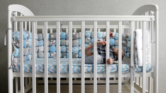 The-happy-kid-lies-in-a-baby-crib-
