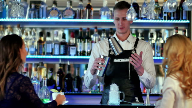 Bartender-is-making-cocktail-at-bar-counter-for-two-girl