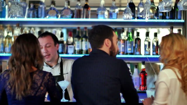 Group-of-friends-relaxing-on-party-in-bar-talking-with-bartender
