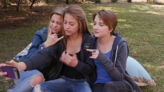 Three-pretty-young-teenage-girls-taking-selfies-on-their-phone-and-having-fun-in-a-park