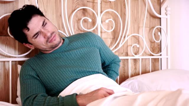Hombre-joven-con-dolor-de-espalda-sentado-en-la-cama-relajantes