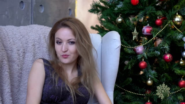 Surprised-young-woman-shouting-over-christmas-tree-background-Looking-at-camera