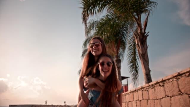 Teenage-girls-having-fun-with-piggyback-ride-on-summer-vacations