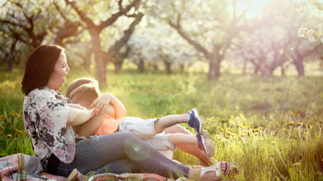 Beautiful-mother-and-her-little-daughter-and-son-outdoors