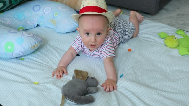 Cute-5-Month-Old-Baby-Boy-With-His-Straw-Hat-On-A-Play-Mat