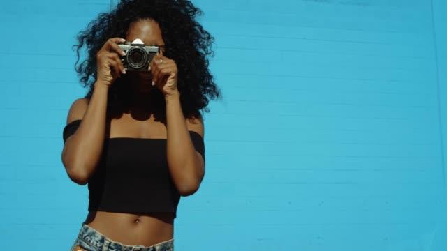 Schöne-junge-Frau-Fotografieren-mit-Film-Kamera-an-bunten-blauen-Wand
