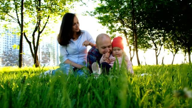 Familia-feliz-está-descansando-en-la-naturaleza-Los-padres-juegan-con-una-hija-pequeña-en-un-parque-en-el-verano-en-puesta-de-sol-movimiento-de-la-cámara