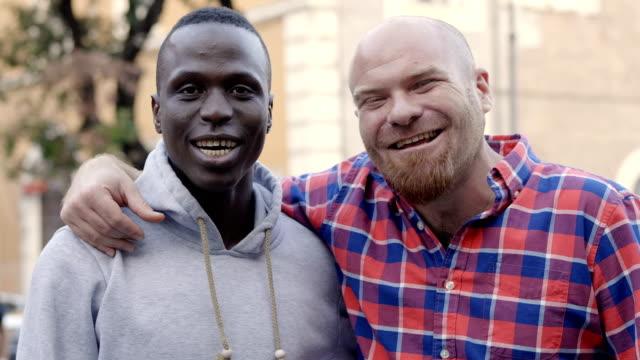 Schwarze-und-weiße-Freunde-umarmen-zusammen-lachen