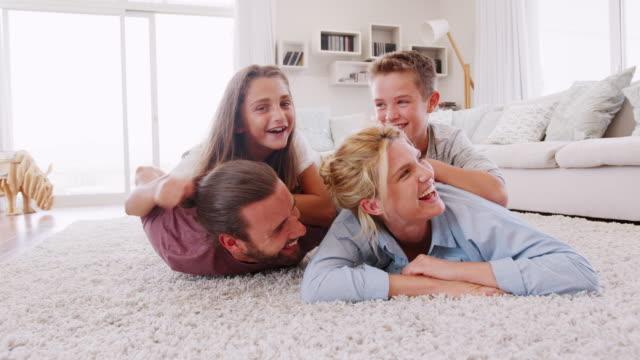 Retrato-de-niños-en-los-padres-fomenta-en-alfombra-en-el-salón-en-casa-filmada-en-cámara-lenta