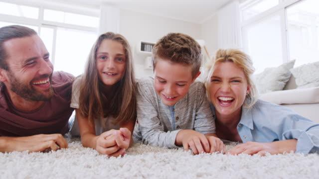Retrato-de-familia-acostado-alfombra-en-salón-casa-filmada-en-cámara-lenta